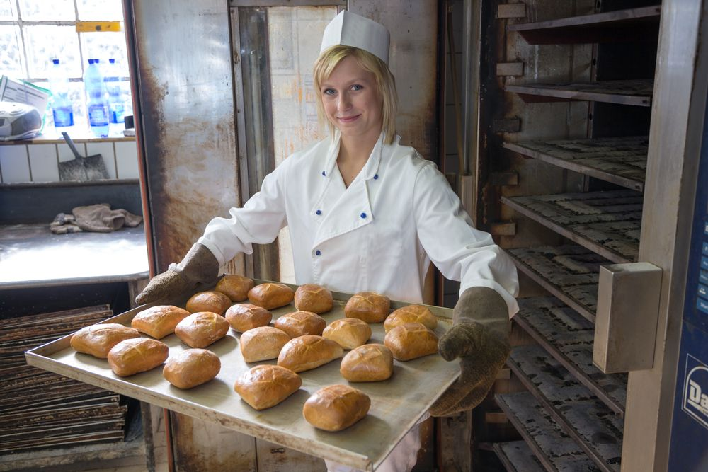 Baker putting a tablet of buns or bread into an oven
